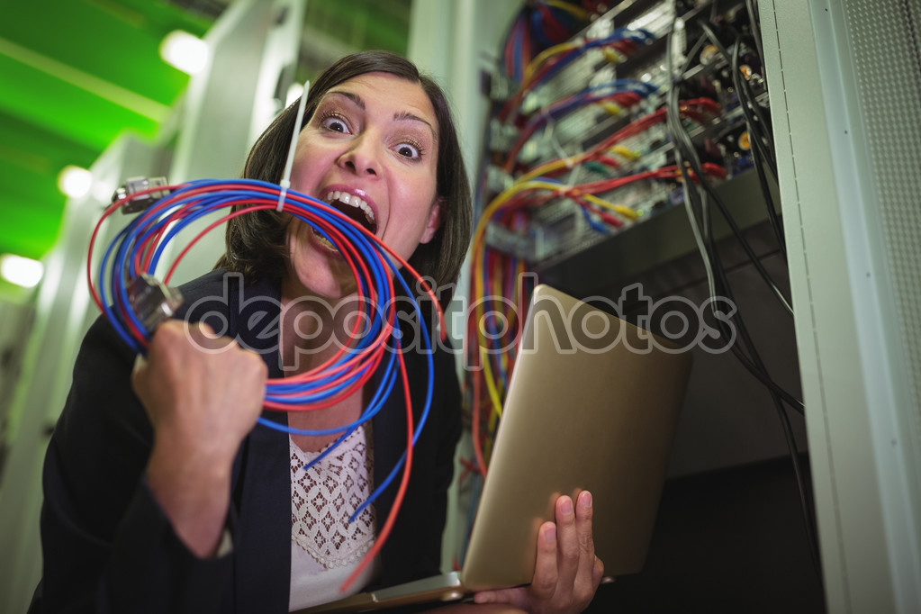 Frustrated technician eating wire and holding laptop